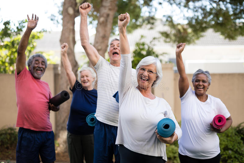 Cheerful multi-ethnic seniors with exercise mats at park royalty free stock image
