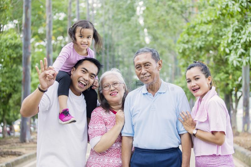 Cheerful multi generation family looks at the camera. Picture of cheerful multi generation family looking at the camera while standing on the road. Shot at the stock photo