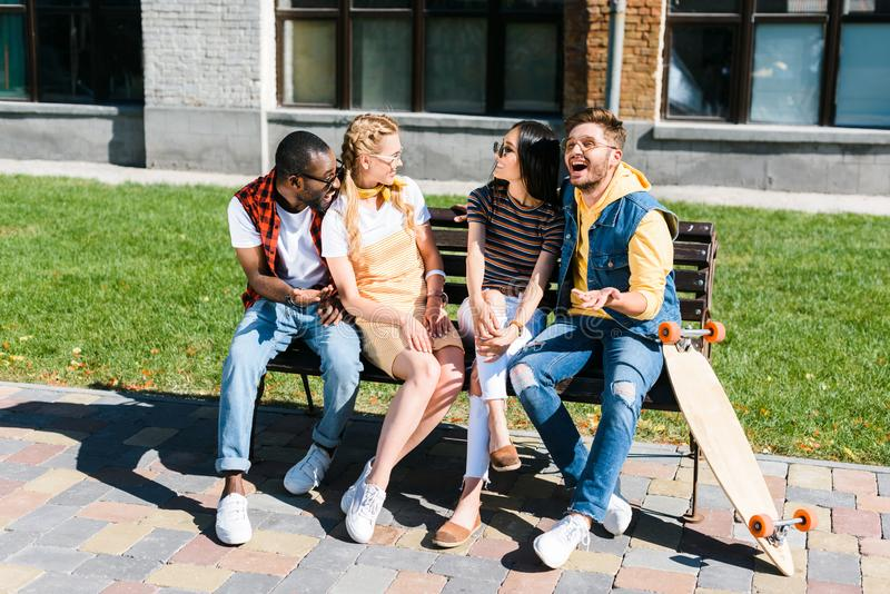Cheerful multicultural couples resting on bench together. On street royalty free stock photography