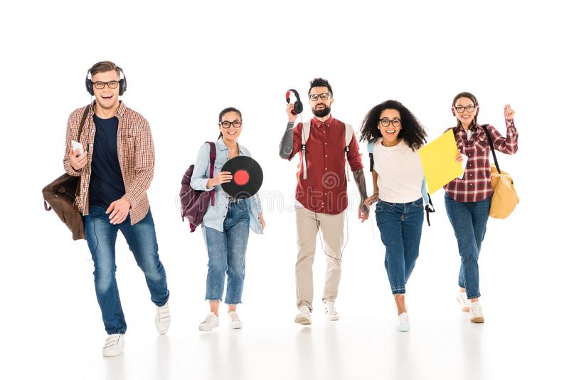 cheerful multicultural group of young people with vinyl records and headhphones isolated stock photography