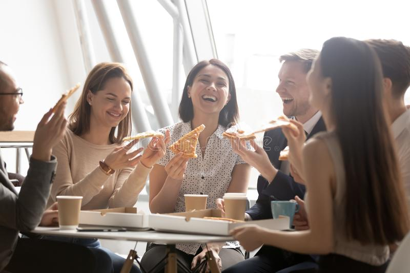 Cheerful multicultural team workers laugh share lunch meal eating pizza. Cheerful multicultural team business people workers laugh share lunch meal eating pizza royalty free stock photo