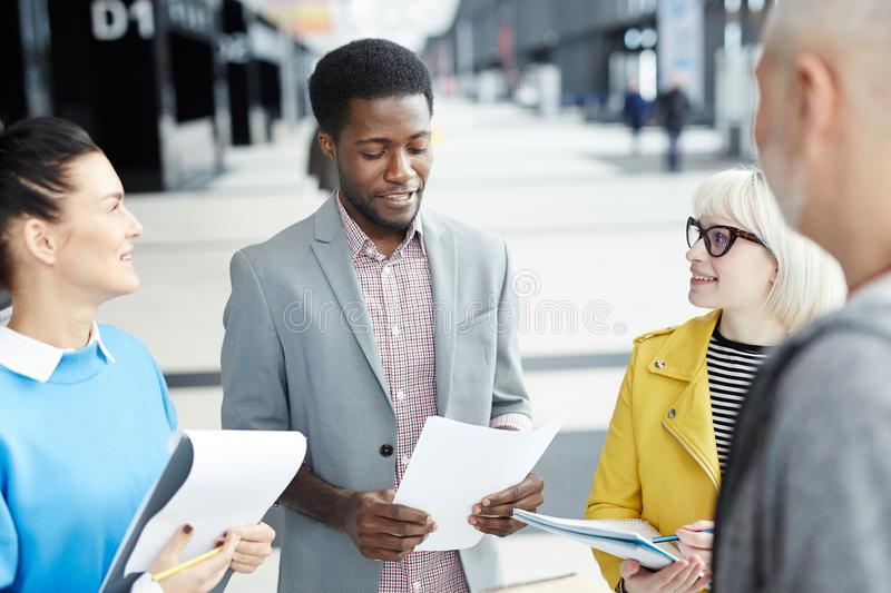Coworkers with documents in office hall stock photography