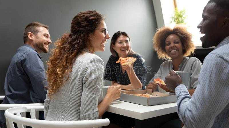 Cheerful multiracial business team people having fun eating pizza together stock photography