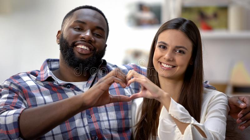 Cheerful multiracial couple showing heart sign made with hands at camera, love stock photos