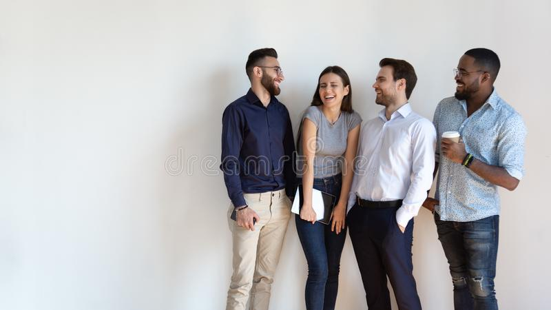 Cheerful multiracial professional business people laughing standing near wall royalty free stock photography