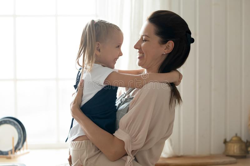 Cheerful mum holding embracing cute little kid daughter at home royalty free stock photo