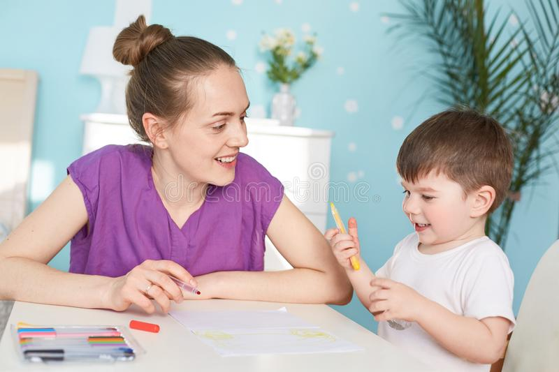 Cheerful mum and son paint together, sit at table, like creativity, spend free time at home, use colourful pencils, look positivel royalty free stock photos
