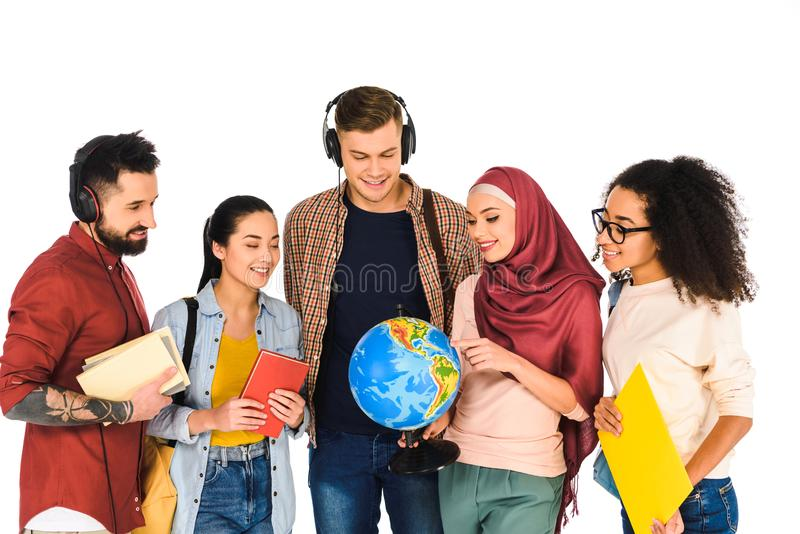 cheerful muslim woman holding globe and standing with multicultural group of people isolated royalty free stock images