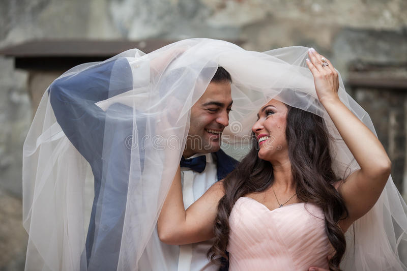 Cheerful newlywed couple, bride and groom, having fun and smiling under veil royalty free stock photography