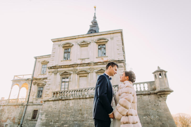 The cheerful newlywed couple is holding hands at the background of the antique gothic mansion. The down side view. stock photography