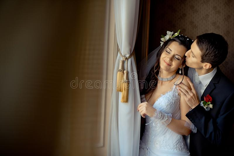 Cheerful newlywed couple is tenderly hugging near the old rich window. The handsome groom is gently kissing his lover in stock photos