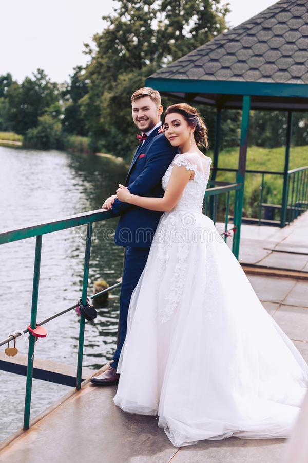 Cheerful newlyweds stand on the pier in an embrace royalty free stock images