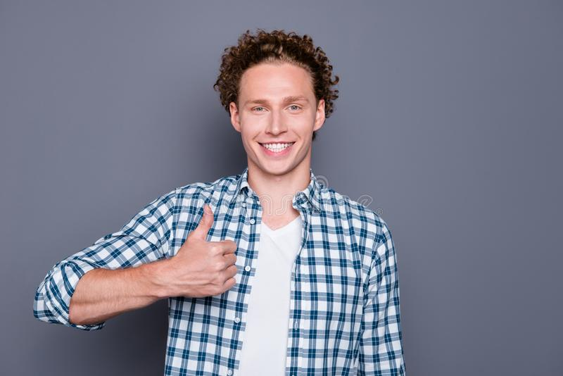 Cheerful nice attractive good-looking handsome young man with wa. Vy hair in casual checkered shirt, showing thumb-up. over grey background royalty free stock photos