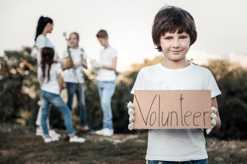 Cheerful nice boy being a volunteer royalty free stock photography