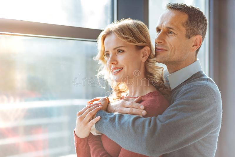 Cheerful nice couple looking into the window royalty free stock photography