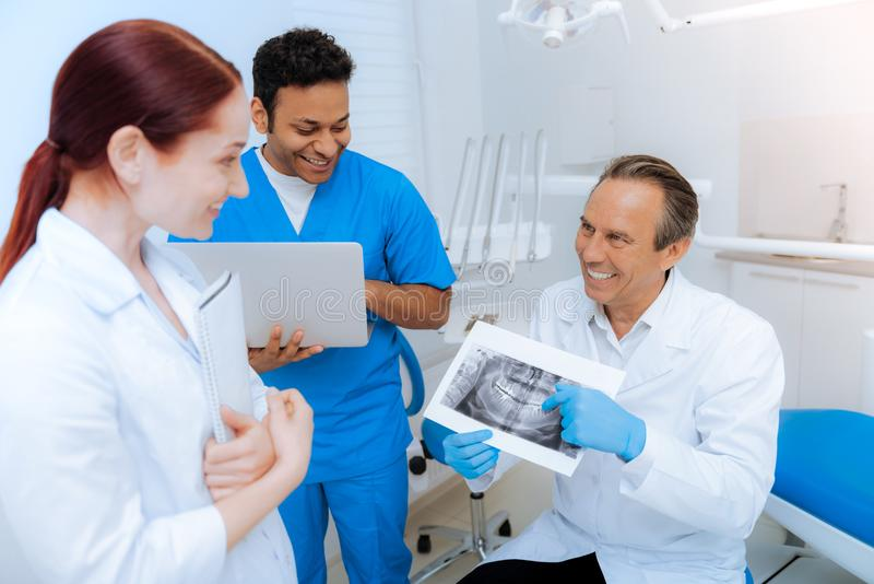 Cheerful nice dentist showing an X ray scan to his colleagues. Professional diagnostics. Cheerful nice male dentist shoeing an X ray scan to his colleagues and royalty free stock image