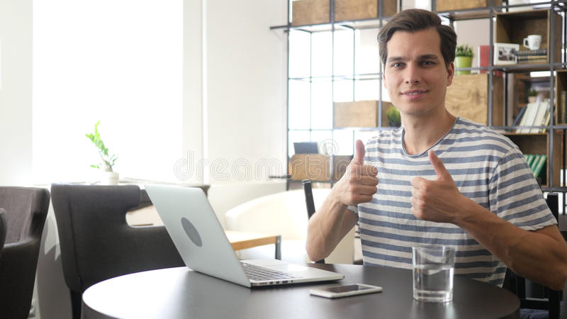 Cheerful office worker at desk doing thumb up sign and smiling. Real workplace stock image