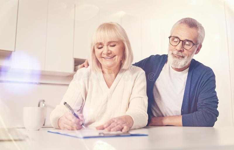 Cheerful old couple signing insurance contract stock images