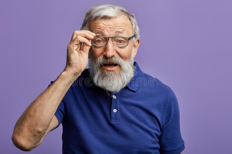 Cheerful old man looking through the glasses at the camera royalty free stock photo