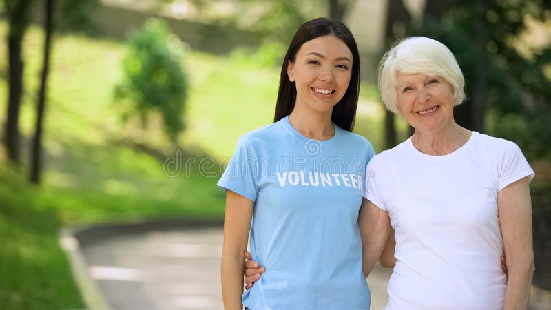 Cheerful old woman and young female volunteer smiling on camera, charity support royalty free stock image