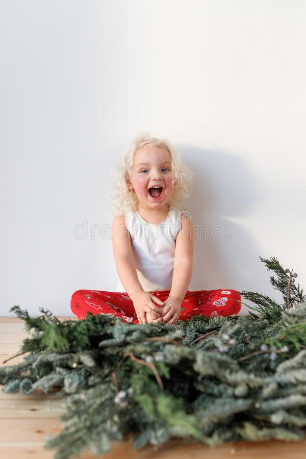 Cheerful overjoyed blonde female child sits crossed legs and Christmas garland in foreground, isolated over pink stock photo