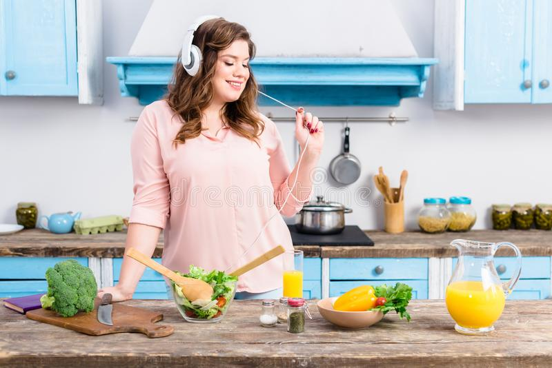 cheerful overweight woman listening music in headphones at table with fresh vegetables in kitchen royalty free stock image