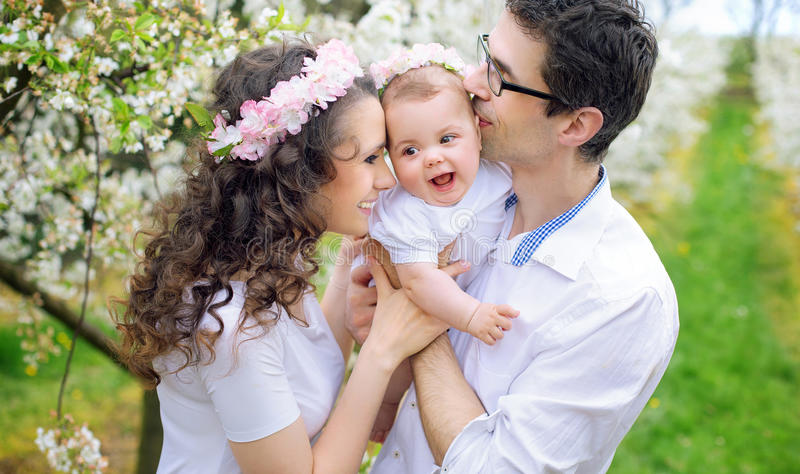 Cheerful parents kissing their beloved child stock images