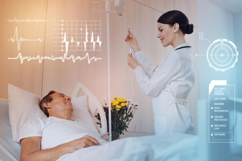 Cheerful patient smiling while a nurse preparing an infusion for him royalty free stock images