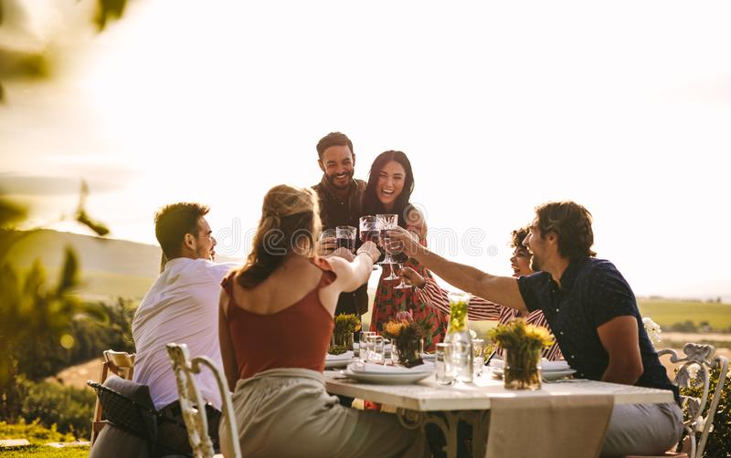 Cheerful people celebrating with drinks at party stock images