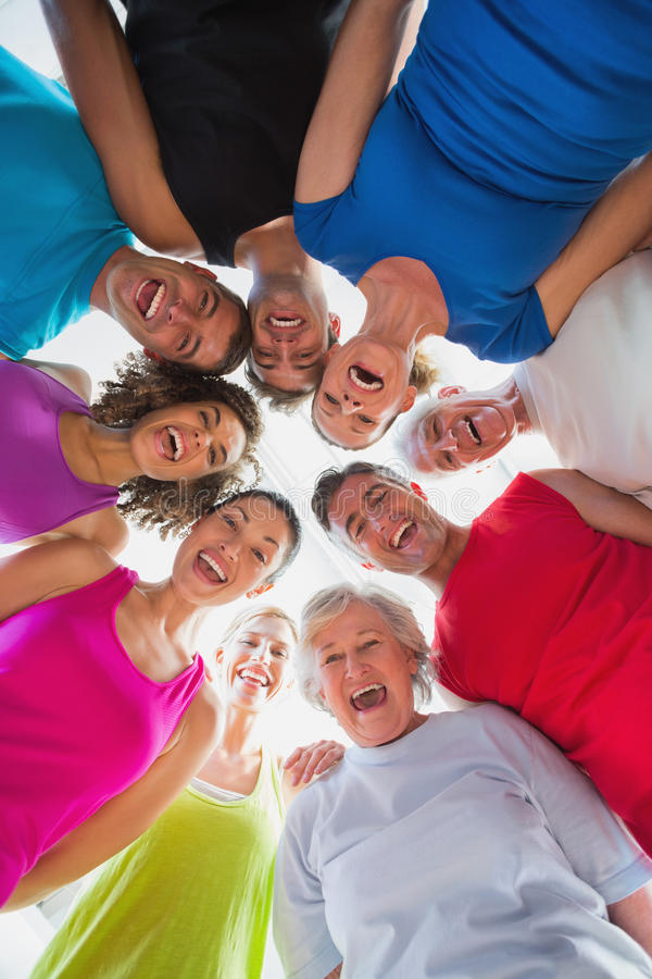 Cheerful people forming huddle at gym. Low angle portrait of cheerful people forming huddle at gym stock photography