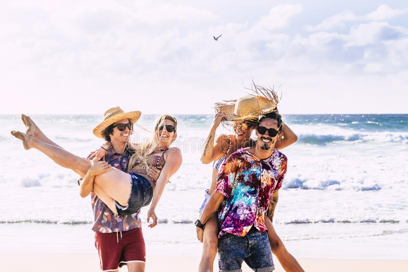 Cheerful people having fun in summer holiday vacation - group of young millennial tourists langh at the beach - men carrying woman royalty free stock image