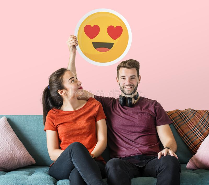 Cheerful couple holding a heart eyes emoticon royalty free stock photo