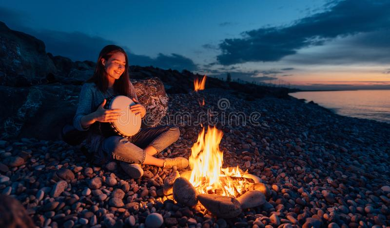 Cheerful percussionist girl playing djembe sitting on beach by the fire at sunset. Cheerful percussionist girl playing djembe sitting on the beach by the fire at royalty free stock photo