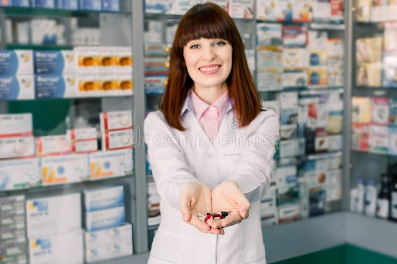 Cheerful pharmacist chemist woman in white coat standing in pharmacy drugstore and holding in her hands many colorful royalty free stock image
