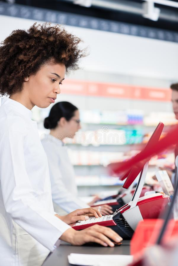 Cheerful pharmacist holding two packs of medicine and giving advices stock photo