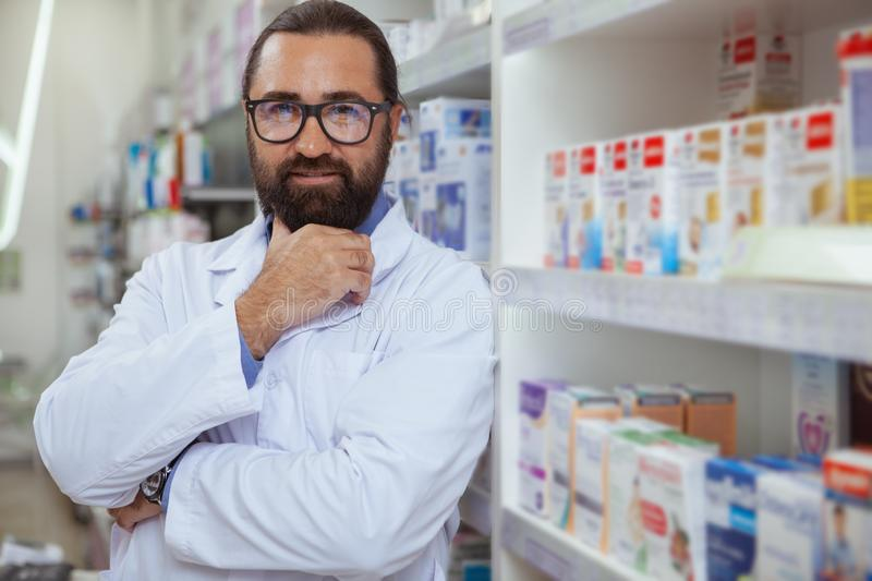Cheerful pharmacist selling medication at his drugstore royalty free stock images