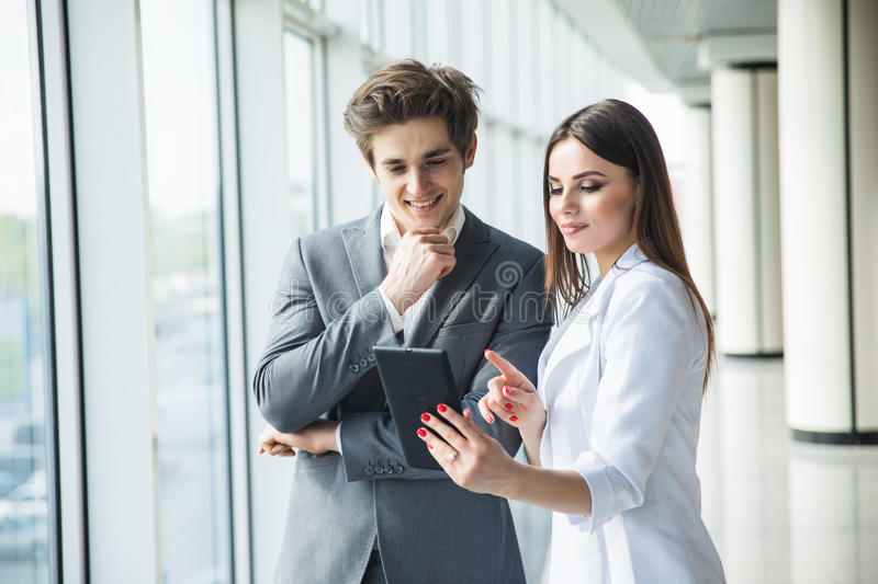 Cheerful business woman and man working together on tablet in office hall stock photography