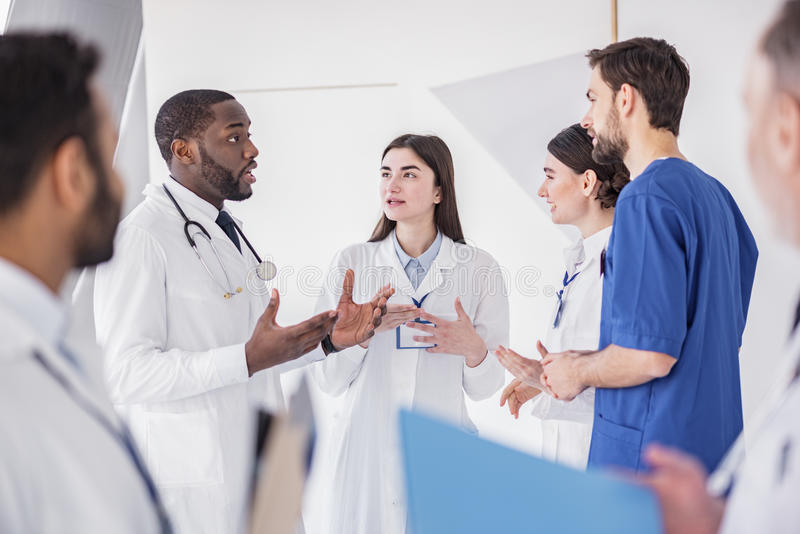 Cheerful physicians speaking at conference in clinic. Outgoing doctors speaking on pause during meeting in office of hospital. Serious african doctor flourishing stock photos
