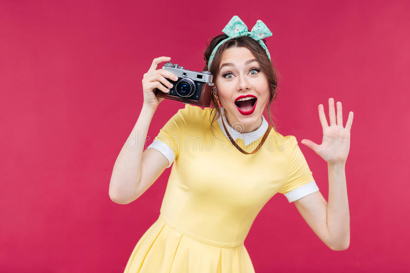 Cheerful pinup girl using vintage camera and taking pictures. Cheerful charming pinup girl in yellow dress using vintage camera and taking pictures over pink stock images