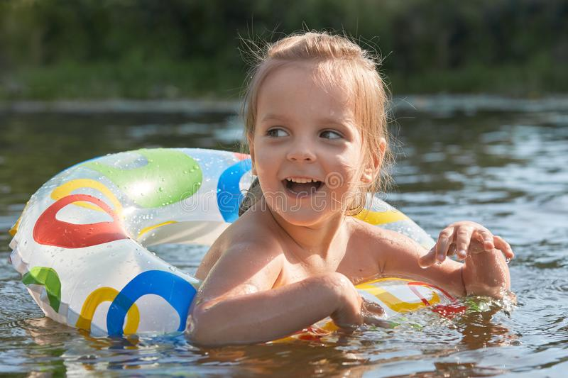 Cheerful playful littl girl swimming with help of swimming circle, opening her mouth widely with excitement, looking aside, royalty free stock images