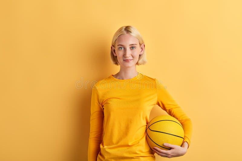 Cheerful pleasant beautiful woman holding basket ball royalty free stock photo