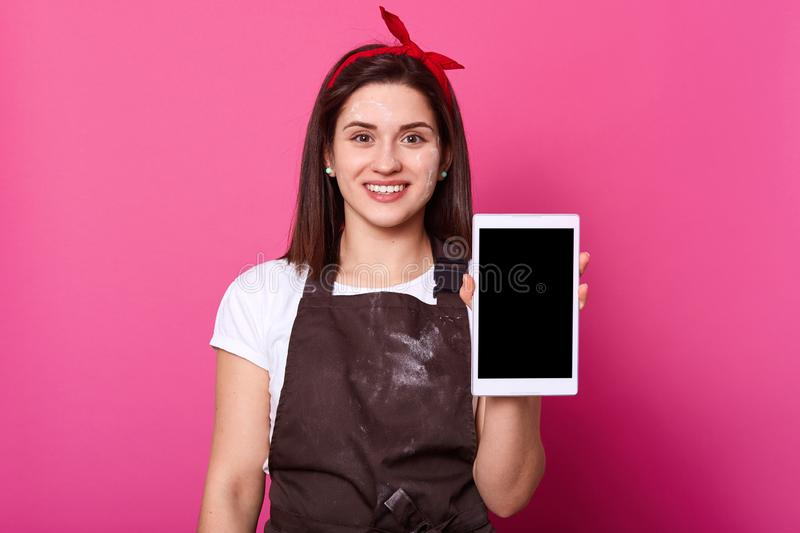 Cheerful pleasant brunette girl stands and presents white tablet, looks happy, Studio isolated portrait of dark haired attractive royalty free stock image