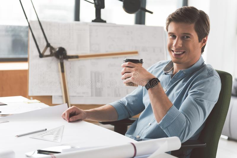 Cheerful pleasant engineer is making pause at work. Coffee time. Portrait of positive young skillful man is sitting at desk and drinking espresso while looking royalty free stock photography