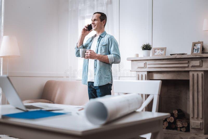 Cheerful pleasant man making a call stock photo