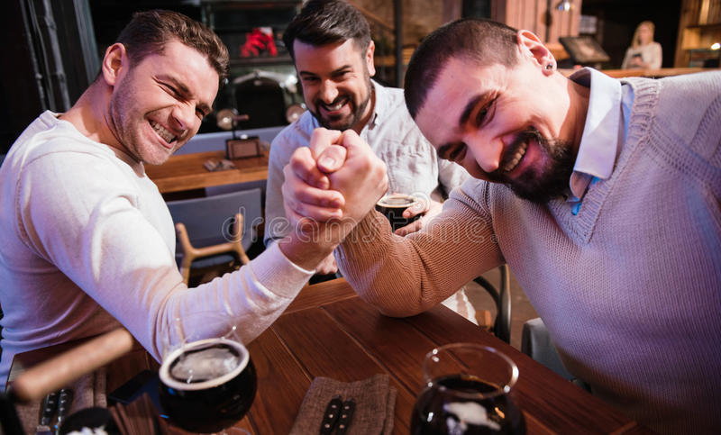Cheerful pleasant men armwrestling in the pub. Who will win. Cheerful pleasant strong men gathering their strength and trying to defeat each other while stock photo