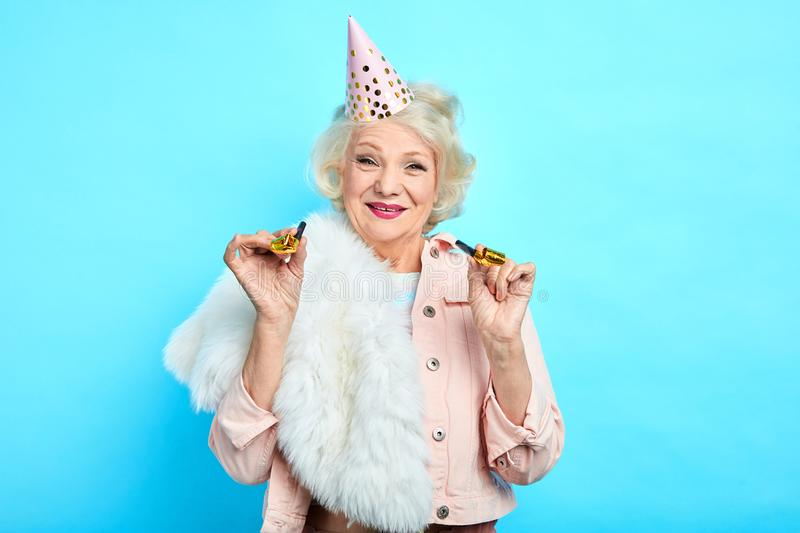 Cheerful pleasant pretty old lady holding party horns and looking at the camera stock images