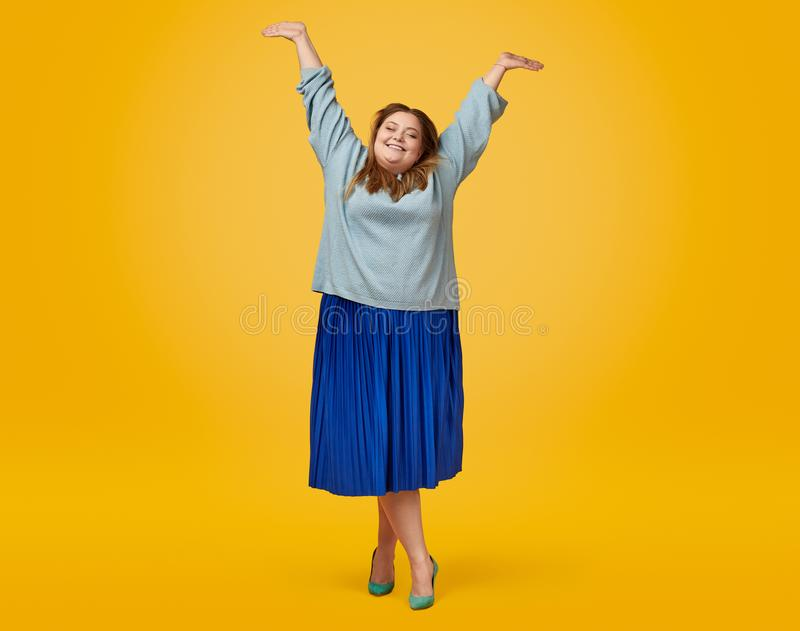 Cheerful plump female with raised hands royalty free stock images