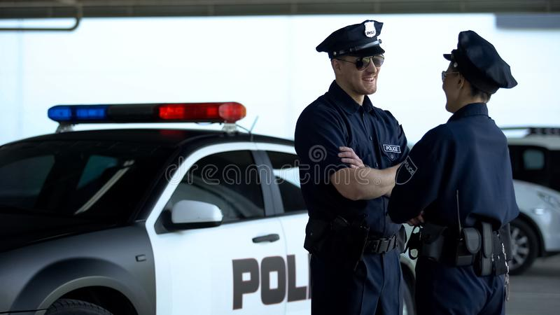 Cheerful policeman and policewoman communicating on parking lot, patrolling royalty free stock photos