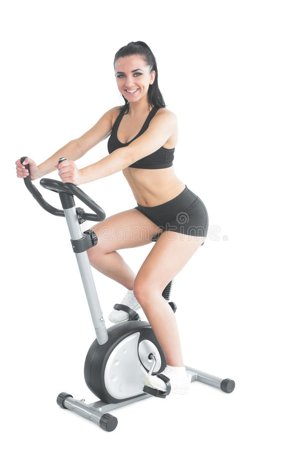 Cheerful ponytailed sporty woman training on an exercise bike royalty free stock photography