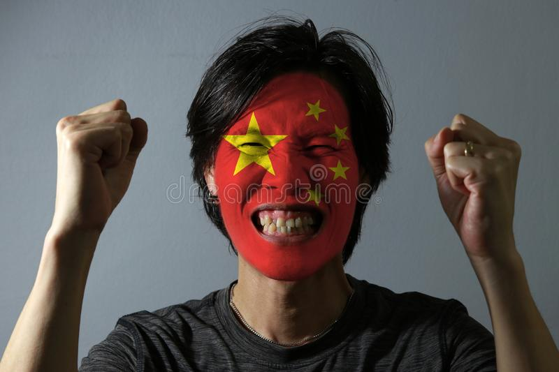 Cheerful portrait of a man with the flag of the China painted on his face on grey background. The concept of sport or nationalism. royalty free stock photos